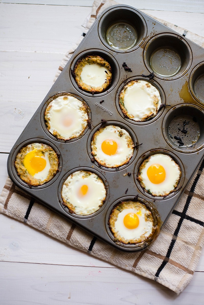 Eight baked eggs in squash nests set in muffin tins, ready to be served