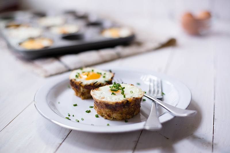 Side angle photo of two baked eggs in squash nests served on a white plate
