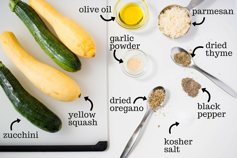 All the ingredients before being combined, including zucchini, yellow squash, olive oil, oregano, kosher salt, thyme, parmesan, garlic powder, and pepper.