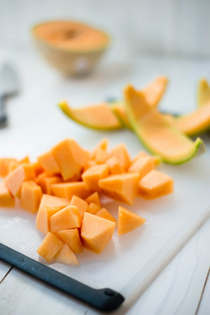 Chunks of cantaloupe placed on a chopping board, ready to be blended in a food processor and make cantaloupe sorbet