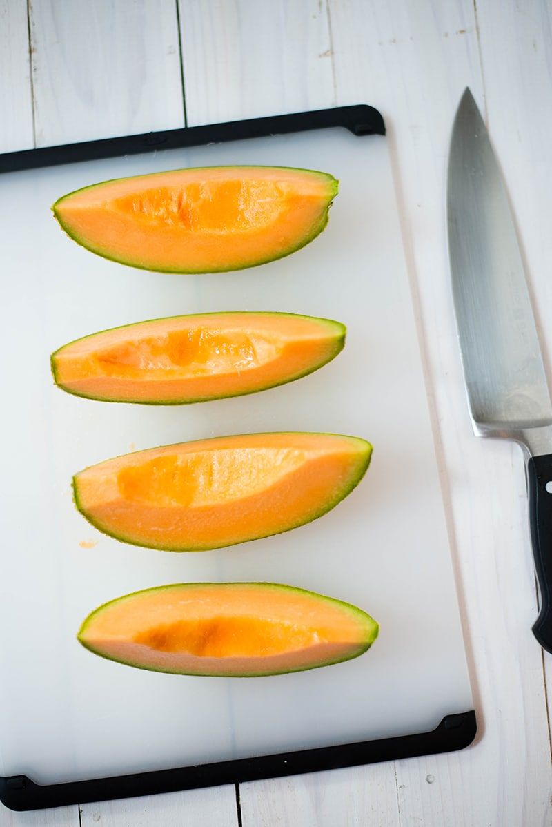 Fresh cantaloupe, the main ingredient in this cantaloupe sorbet recipe, cut into slices and placed on a chopping board