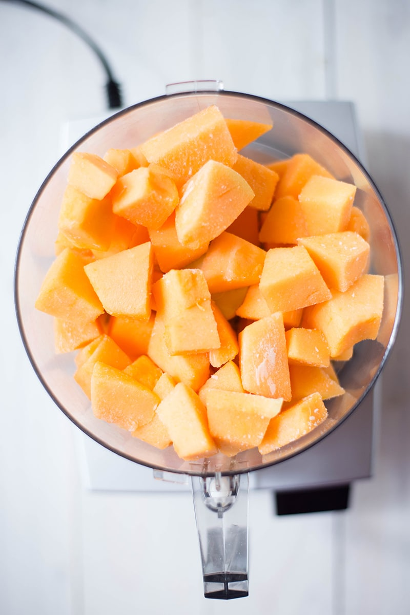Frozen cubes of cantaloupe placed in a food processor, ready to be blended into a soft, cantaloupe sorbet