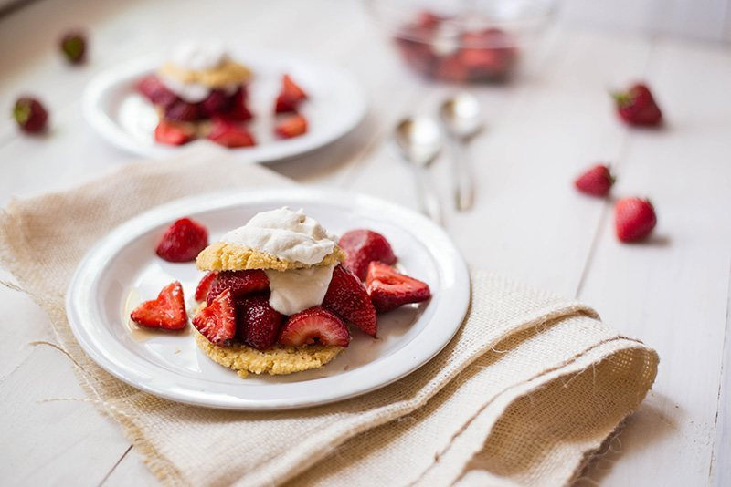 Side angle photo of strawberry shortcake on a white serving plate, garnished with fresh strawberries and topped with vegan whipped cream