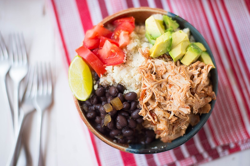 Overhead view of the Slow Cooker Chicken Burrito Bowl, including avocado tomatoes, and black beans.