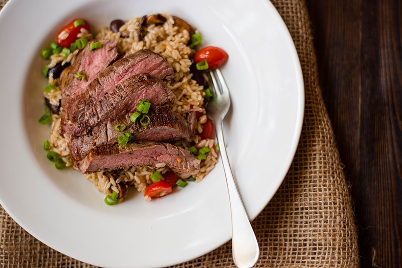 Bowl of brown rice pilaf with flank steak to illustrate how to add meat to your order when trying to eat healthy at restaurants.