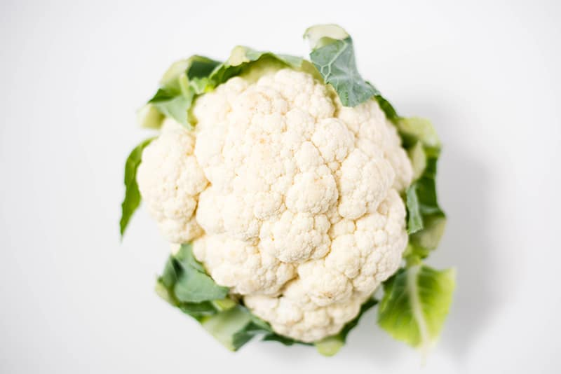 A single fresh cauliflower which still has the leaves attached and can be cut up and cooked in order to make the cauliflower cheese sauce.