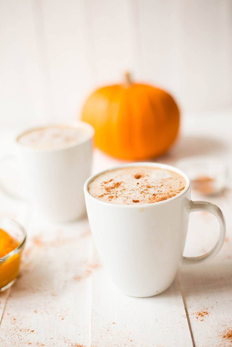 Close up side view of 2 white mugs filled with Healthy Pumpkin Spice Latte, with a pumpkin on the background.