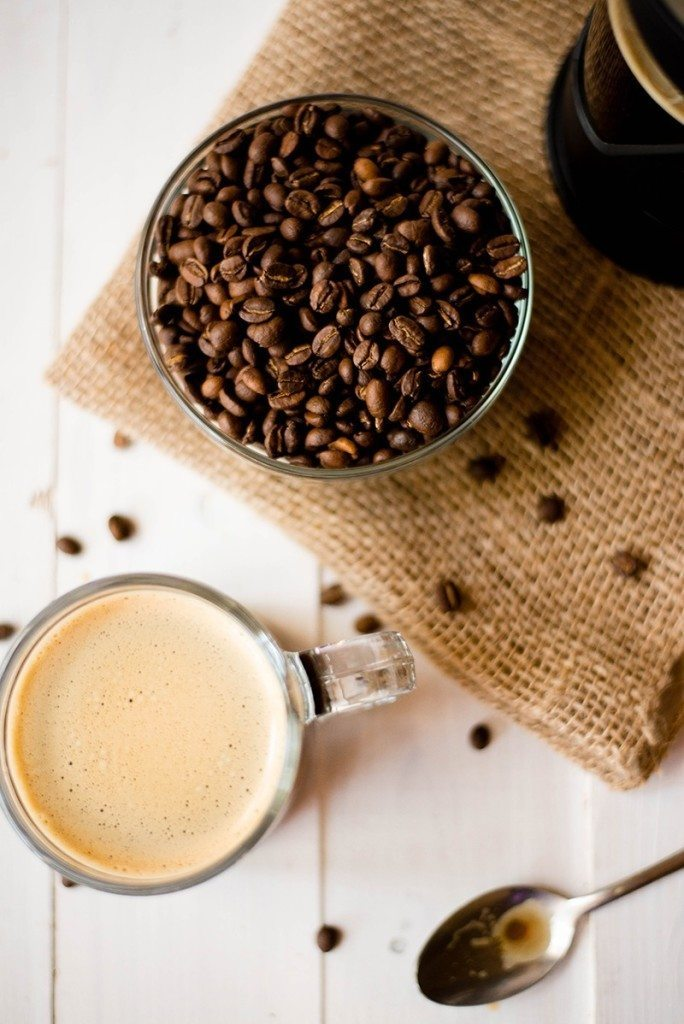 Overhead view of a coffee with homemade creamer beside a bowl of healthy coffee beans.