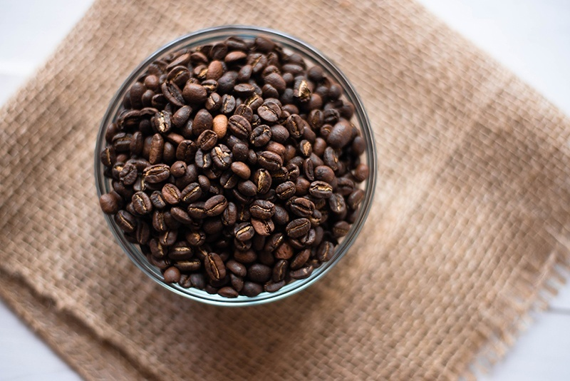 Overhead image of a bowl of fresh, organic coffee beans ready to make a cup of healthy coffee.
