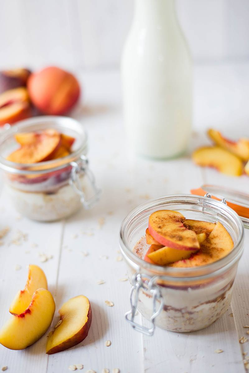Side view of a glass cup with a handle containing Fresh Peach Cobbler Overnight Oats, with slices of peaches as well as whole peaches near the glass cups.