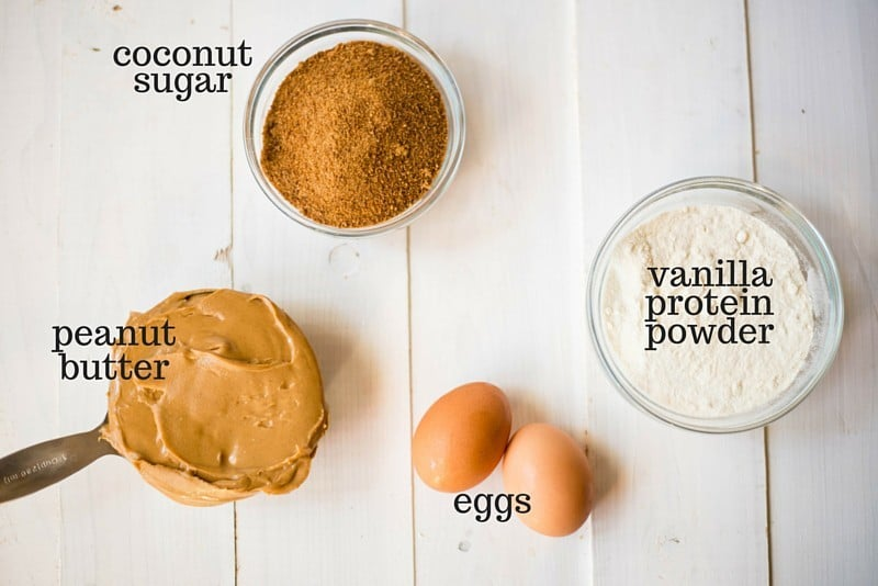 The four easy ingredients you need to make peanut butter protein cookies, including peanut butter, vanilla protein powder, eggs, and coconut sugar.
