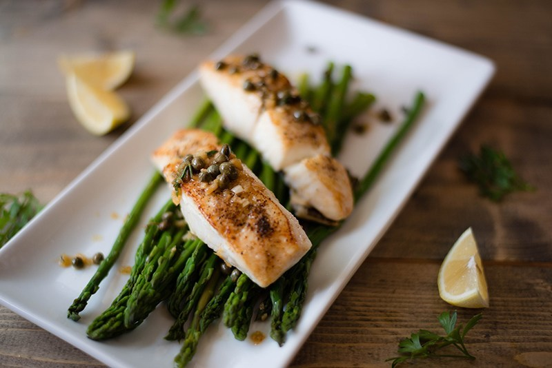 Halibut picatta over steamed asparagus and topped with capers to show how fish is a great menu item when eating out healthy at restaurants.