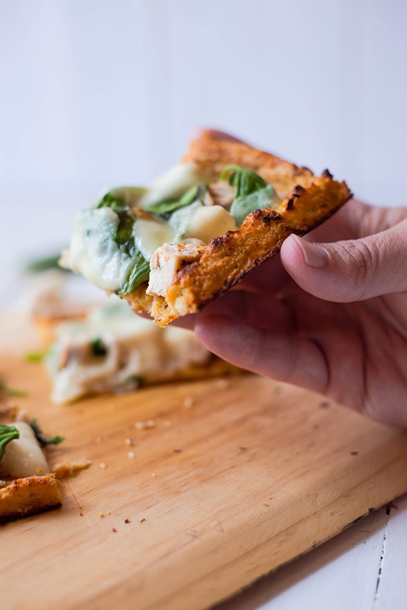 Close up shot of a hand holding one slice of the cauliflower pizza crust to show the golden, crispy edges of the cauliflower pizza crust that is ready to eat and enjoy.