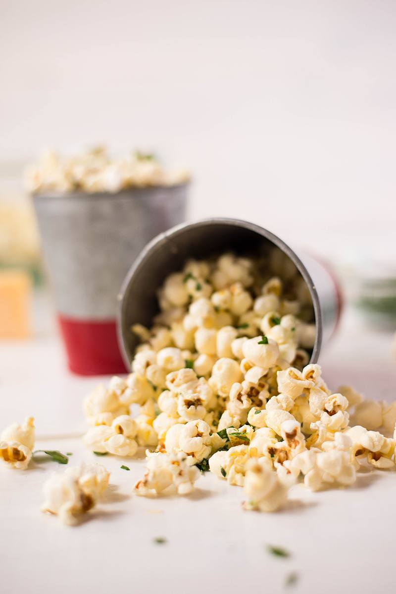 Close up side image of Parmesan And Sea Salt Popcorn tumbling out of a container tipped on its side, with another full container of popcorn in the background.