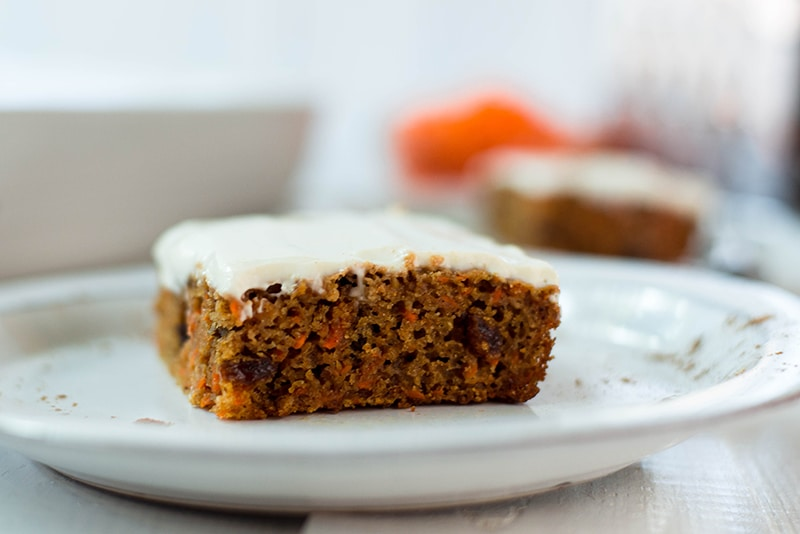 Healthy carrot cake topped with greek yogurt frosting, sliced and ready to be served