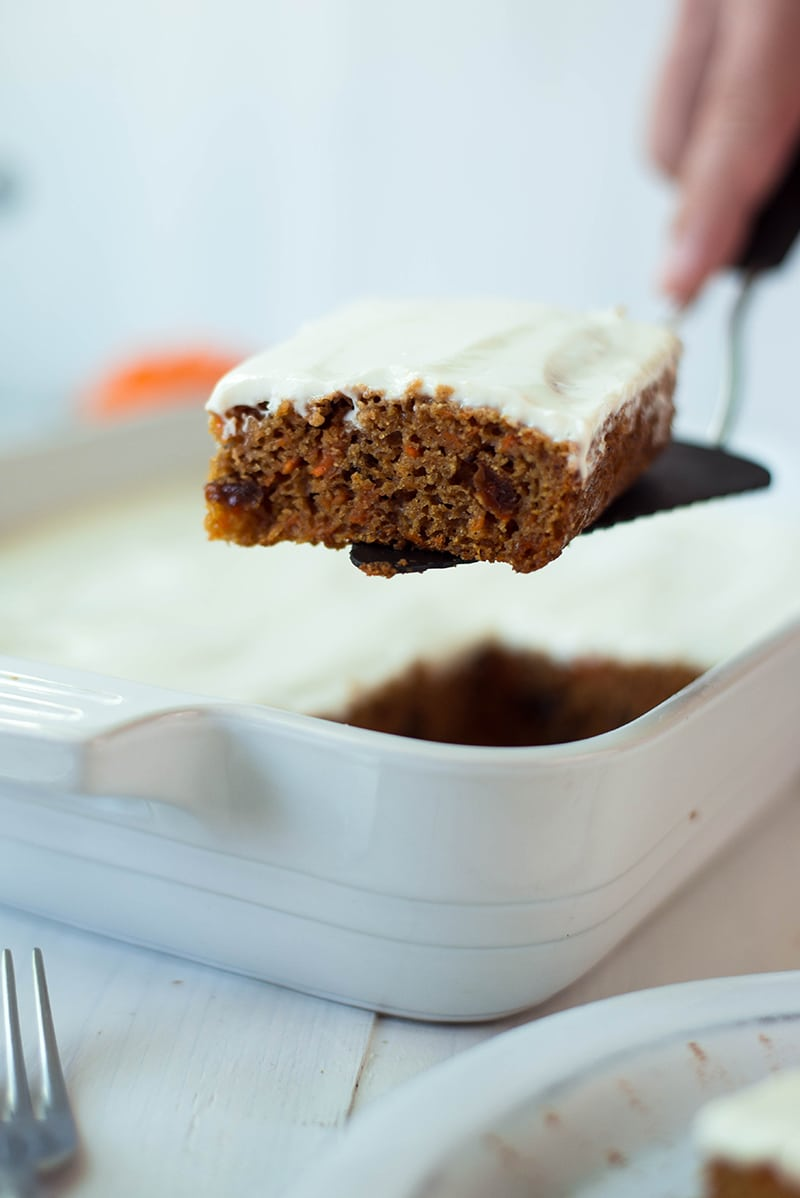 A slice of healthy carrot cake, plated and ready to be enjoyed and topped with a greek yogurt frosting.