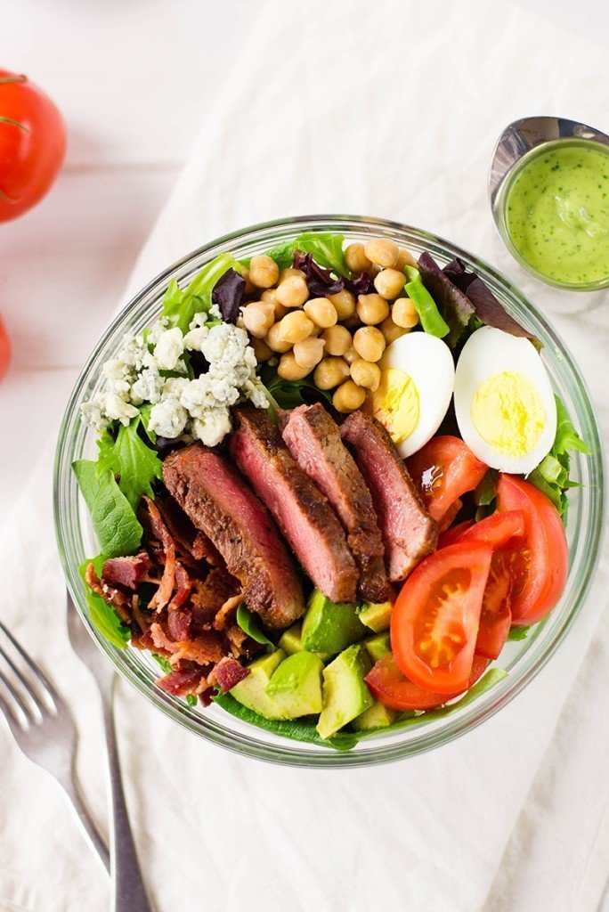 Image of healthy Steak Cobb Salad with creamy avocado lime dressing and including tomatoes, eggs, and avocado.