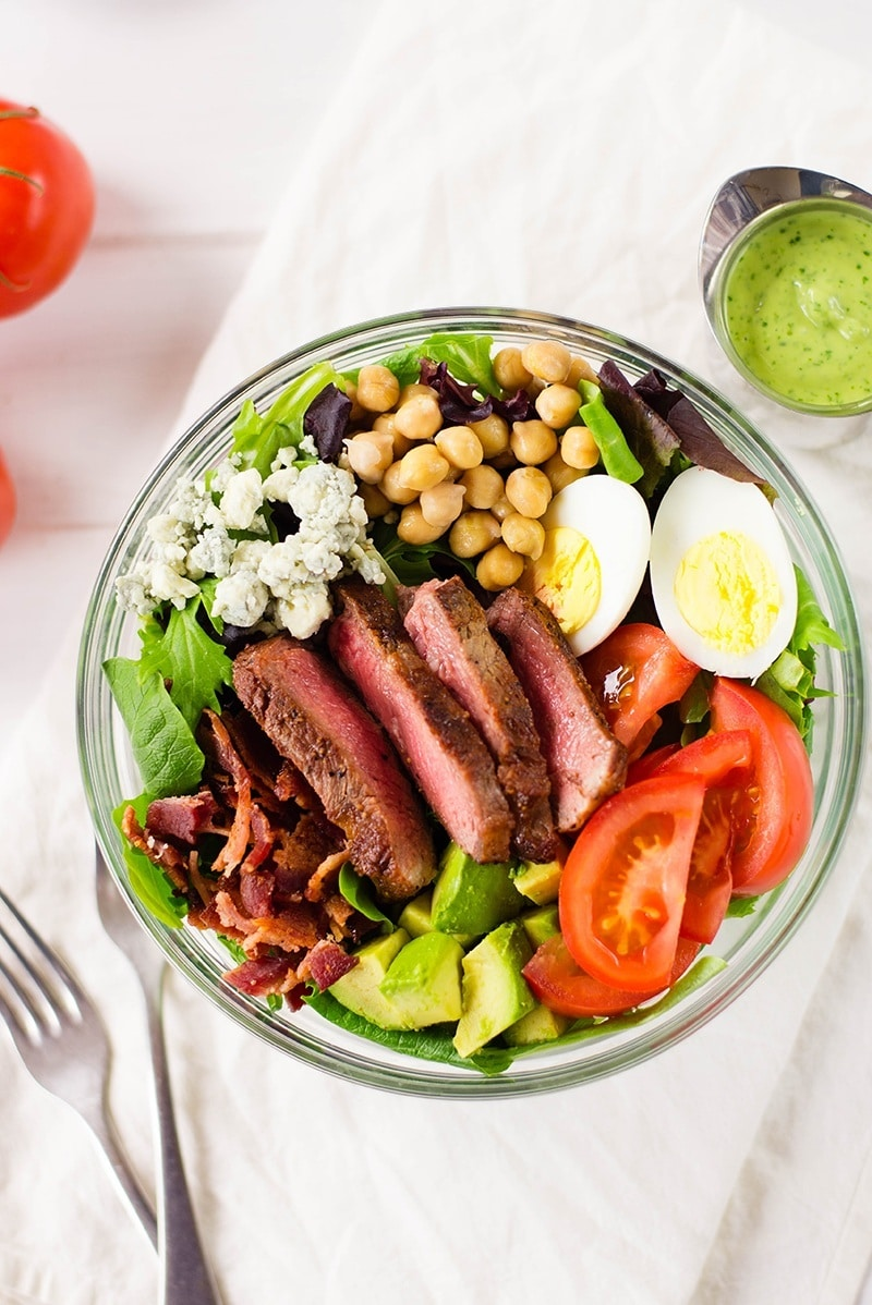 Close up of steak Cobb salad loaded with hard-boiled eggs, tomatoes, garbanzo beans, avocado, bacon strips, and crumbled Gorgonzola cheese