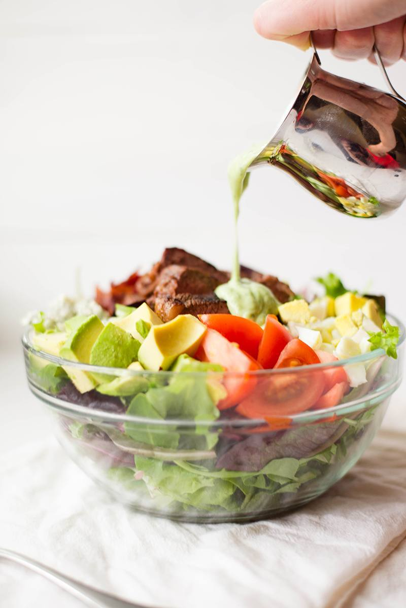 Close up side view of a salad in a clear glass bowl. The salad is made of lettuce, tomatoes, steak, eggs, and avocado and is being drizzled with dressing.
