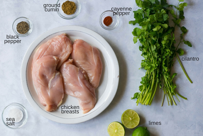 Ingredients set out for the cilantro lime chicken marinade, including sea salt, pepper, cumin, cayenne pepper, cilantro and limes. Also pictured are the chicken breasts which will be marinated.