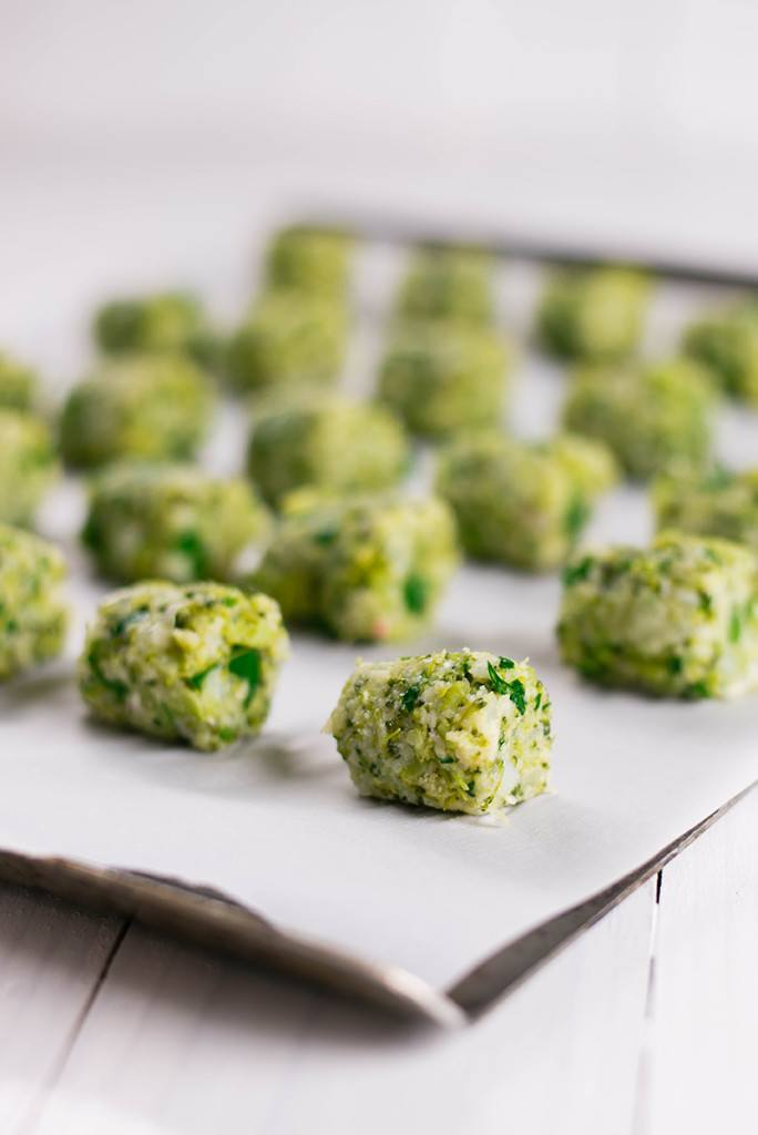 Healthy Baked Broccoli Tots formed and placed on parchment lined baking sheet ready to be baked.
