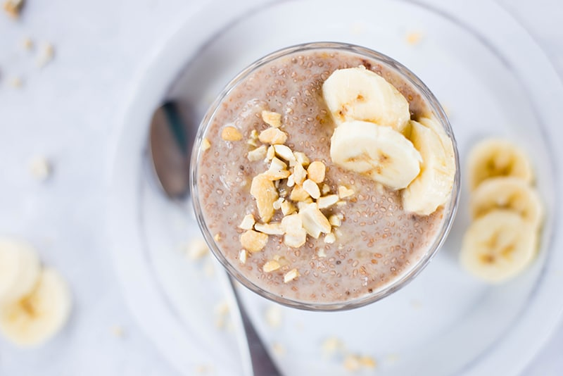 Overhead shot of banana chia pudding served in a mason jar and topped with crushed cashews