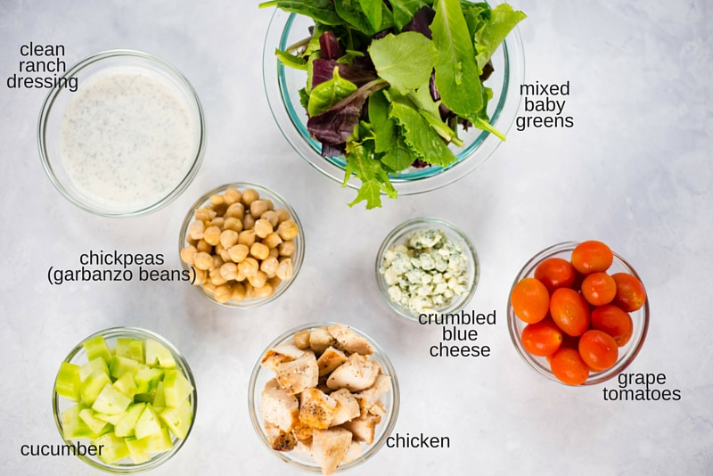 Ingredients used to make Mason jar cobb salad placed in glass bowls and photographed from above