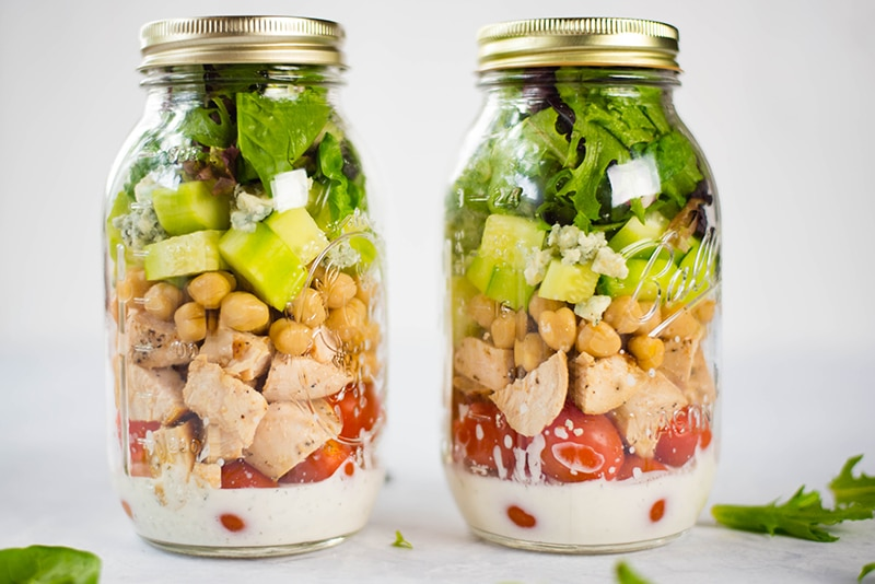 Two Mason jar salads with chicken cobb prepared with leafy greens, chopped cucumber, grape tomatoes, crumbled gorgonzola, garbanzo beans, and clean ranch dressing