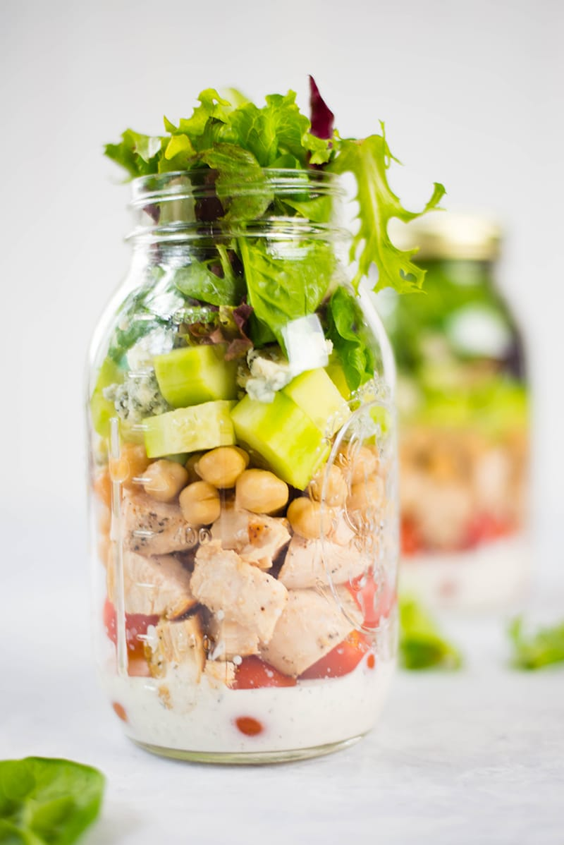 : Homemade ranch dressing, chopped cucumber, grape tomatoes, chickpeas, leafy greens, and grilled chicken, all arranged in layers inside a Mason jar to make chicken cobb Mason jar salad with chicken