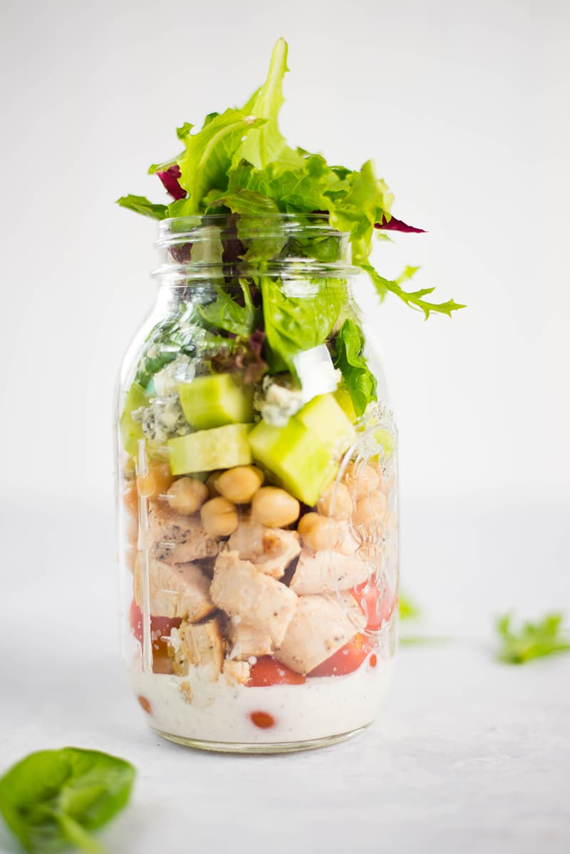 Chicken Cobb salad in a jar, with the lid off, and filled at the top with leafy greens