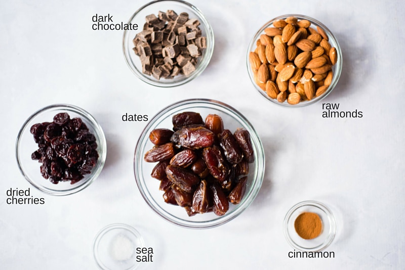 All the ingredients used to make dark chocolate cherries energy bites, placed in glass bowls, including dates, dried cherries, cinnamon, dark chocolate morsels, and raw almonds