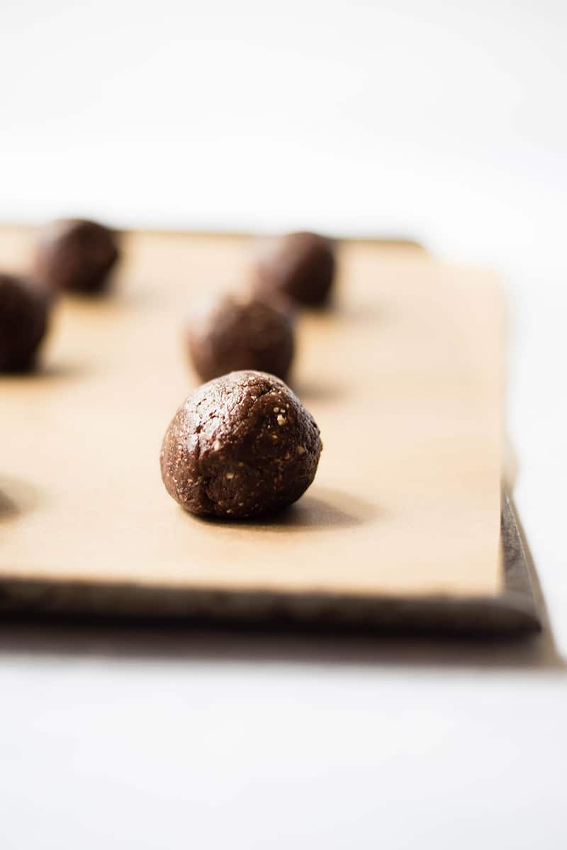 Close up of dark chocolate cherry energy bites placed on a baking sheet