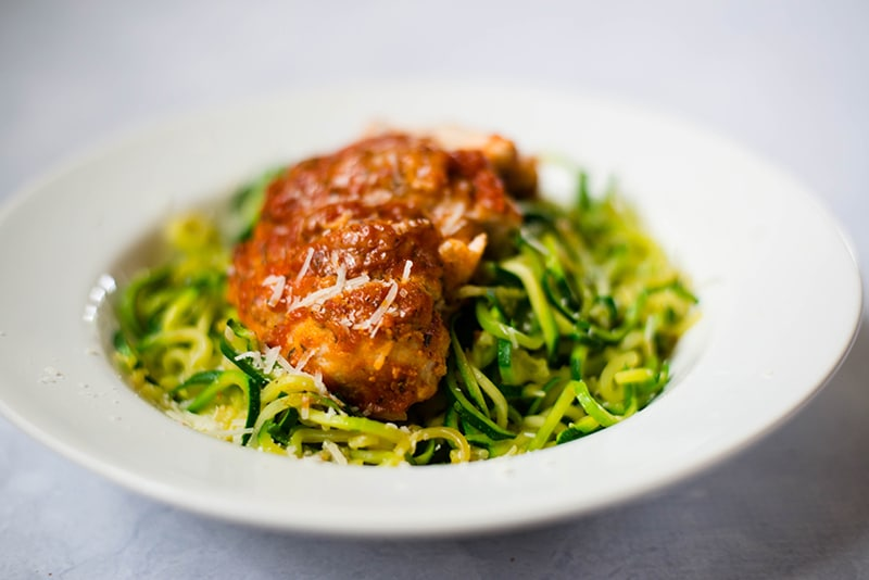 Healthy baked chicken Parmesan placed atop a bed of zucchini noodles, ready to be served and enjoyed