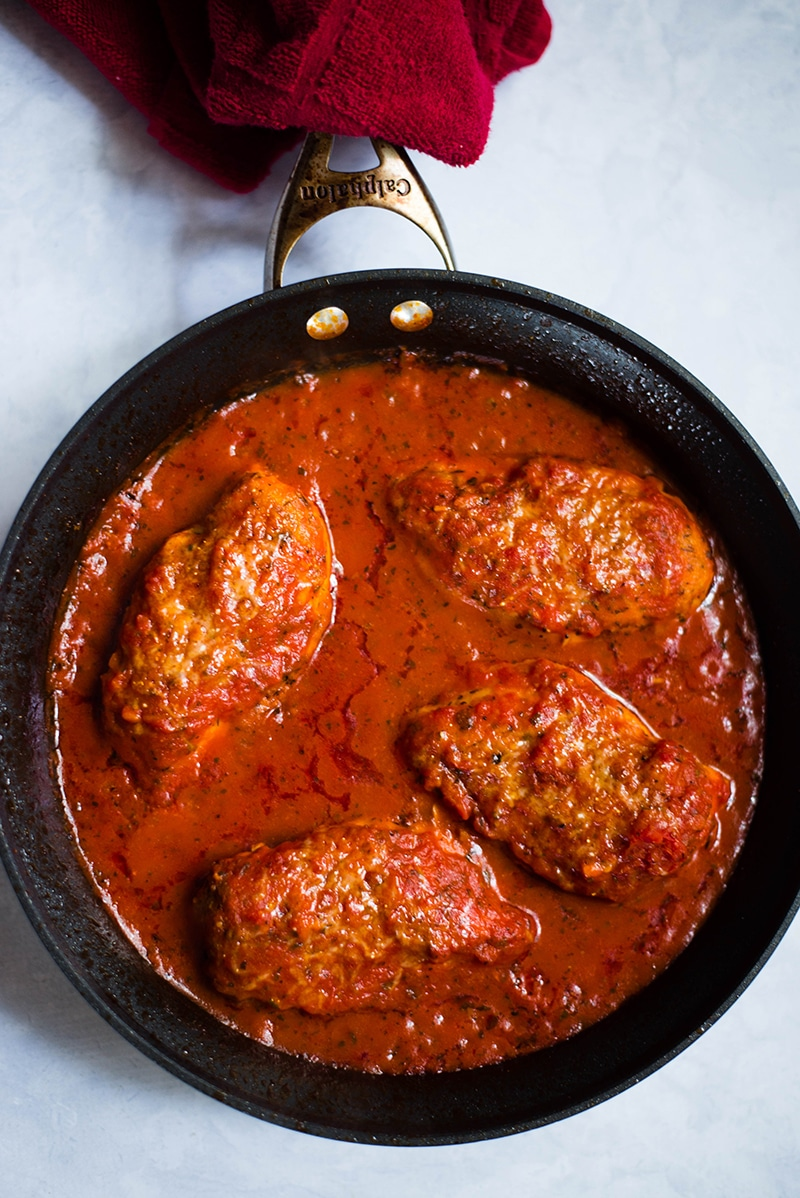 Healthy baked chicken parmesan covered in a thick tomato sauce, simmering in a skillet and ready to be served on a plate of zucchini noodles