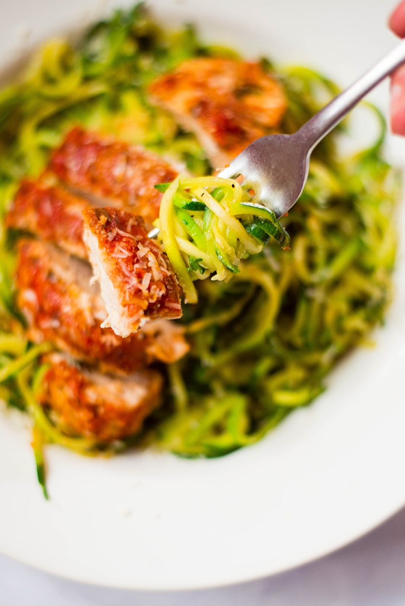 A serving of healthy baked chicken Parmesan and a forkful of zucchini noodles, ready to be enjoyed
