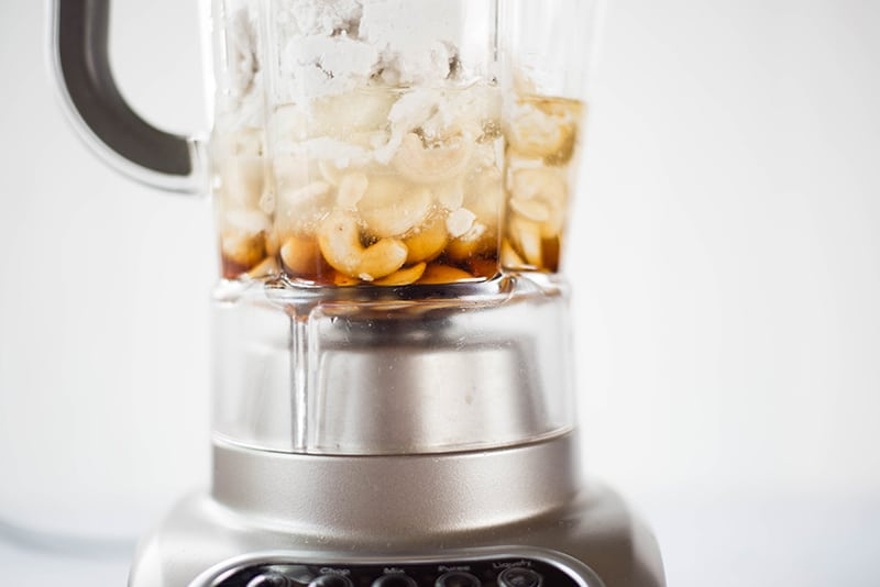 Side view of a blender containing ingredients for the No Bake Cheesecake Recipe, including cashews, coconut milk and maple syrup.