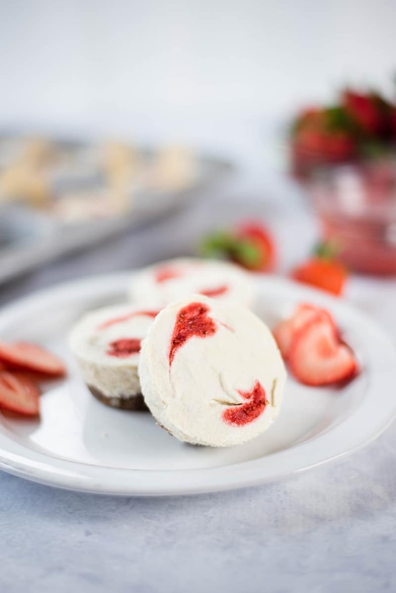 Close up image of a white plate with three mini cheesecakes on it, and a few strawberries sprinkled around.