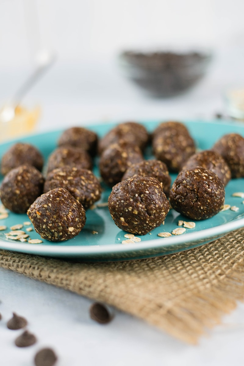 Close up side image of 15 No Bake Chocolate Peanut Butter Energy Balls on a blue plate, with a few chocolate chips near the plate, as a high protein snack perfect for after school.