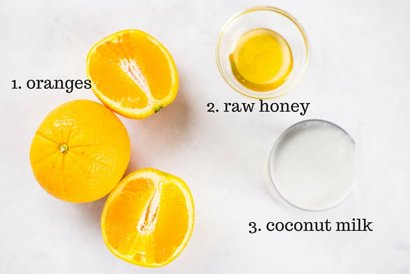 Fresh naval oranges, a bowl of raw honey, and a can of coconut milk – the three ingredients needed to make refreshing orange creamsicles