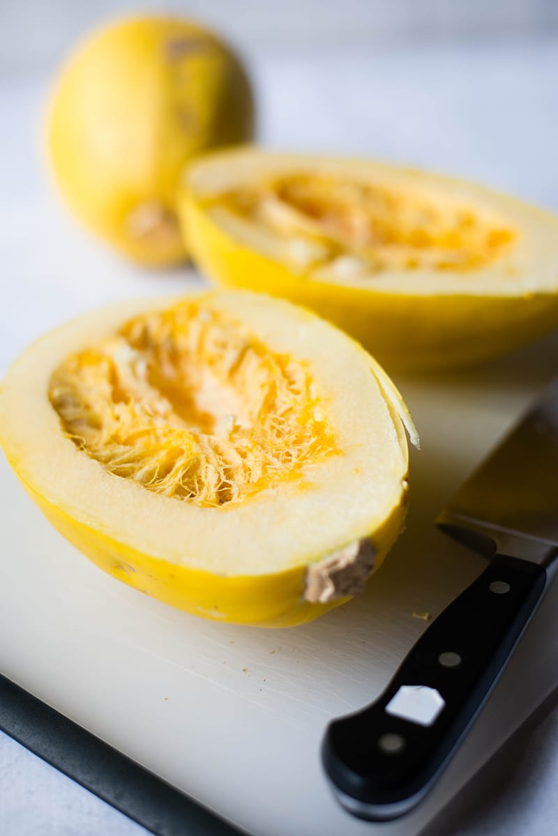 Squash cut in half and placed on a chopping board, ready to be placed in the oven to make spaghetti squash bowls