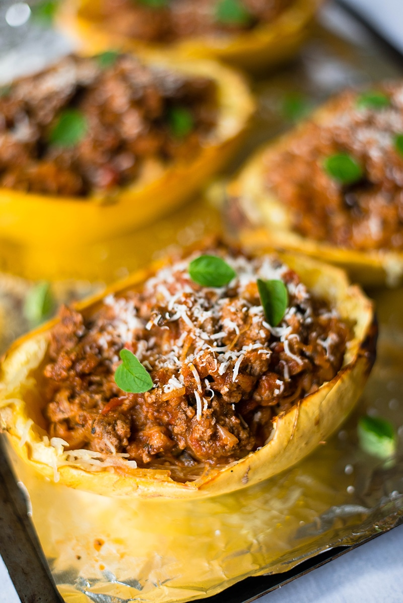 Spaghetti squash bowls stuffed with ground beef marinara sauce, placed on a lined baking sheet, and ready to be served