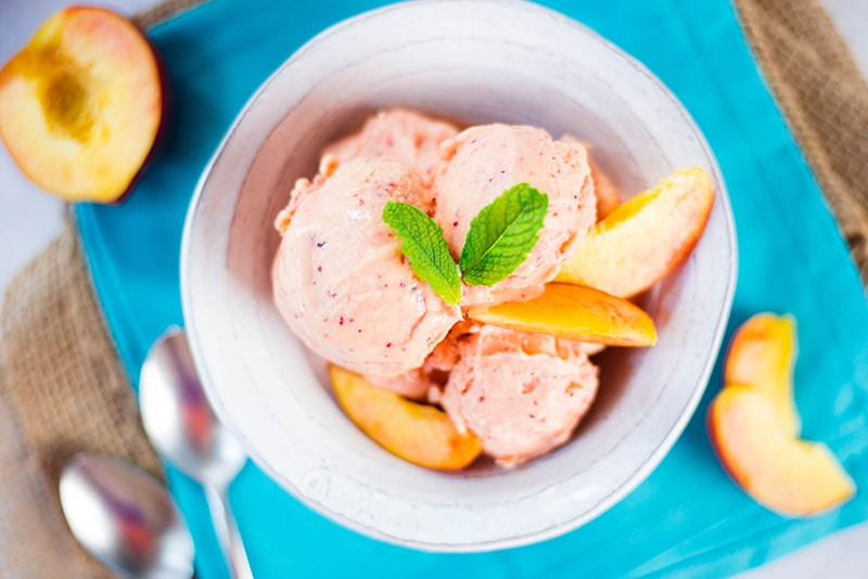 Peach frozen yogurt garnished with mint leaves and fresh peaches, ready to be served