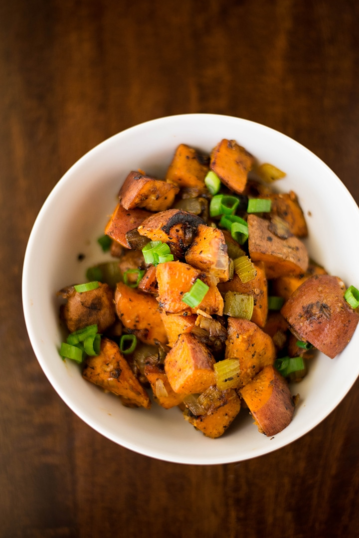 Bowl of sweet potato hash ready to eat, topped with sliced green onions.