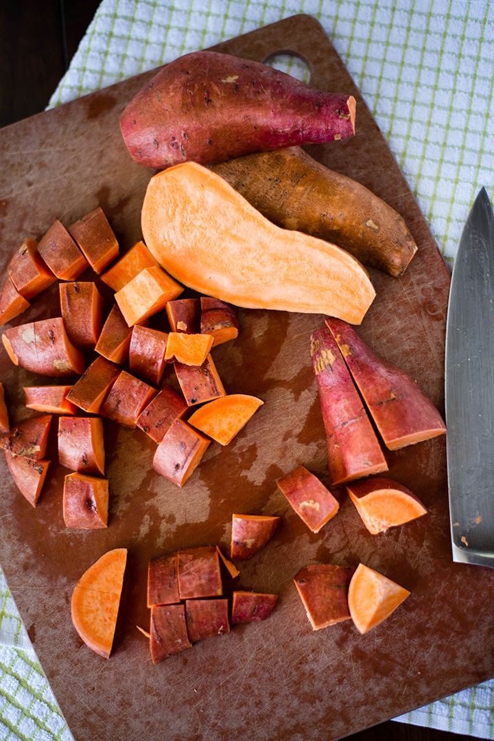 Fresh sweet potatoes, unpeeled, on a cutting board, getting diced to be put into the sweet potato hash recipe.