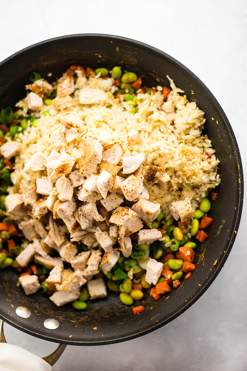 View of a skillet which contains the diced, cooked chicken, cauliflower rice, edamame, carrots, and sliced green beans to show all the ingredients required to make the chicken cauliflower fried rice recipe.