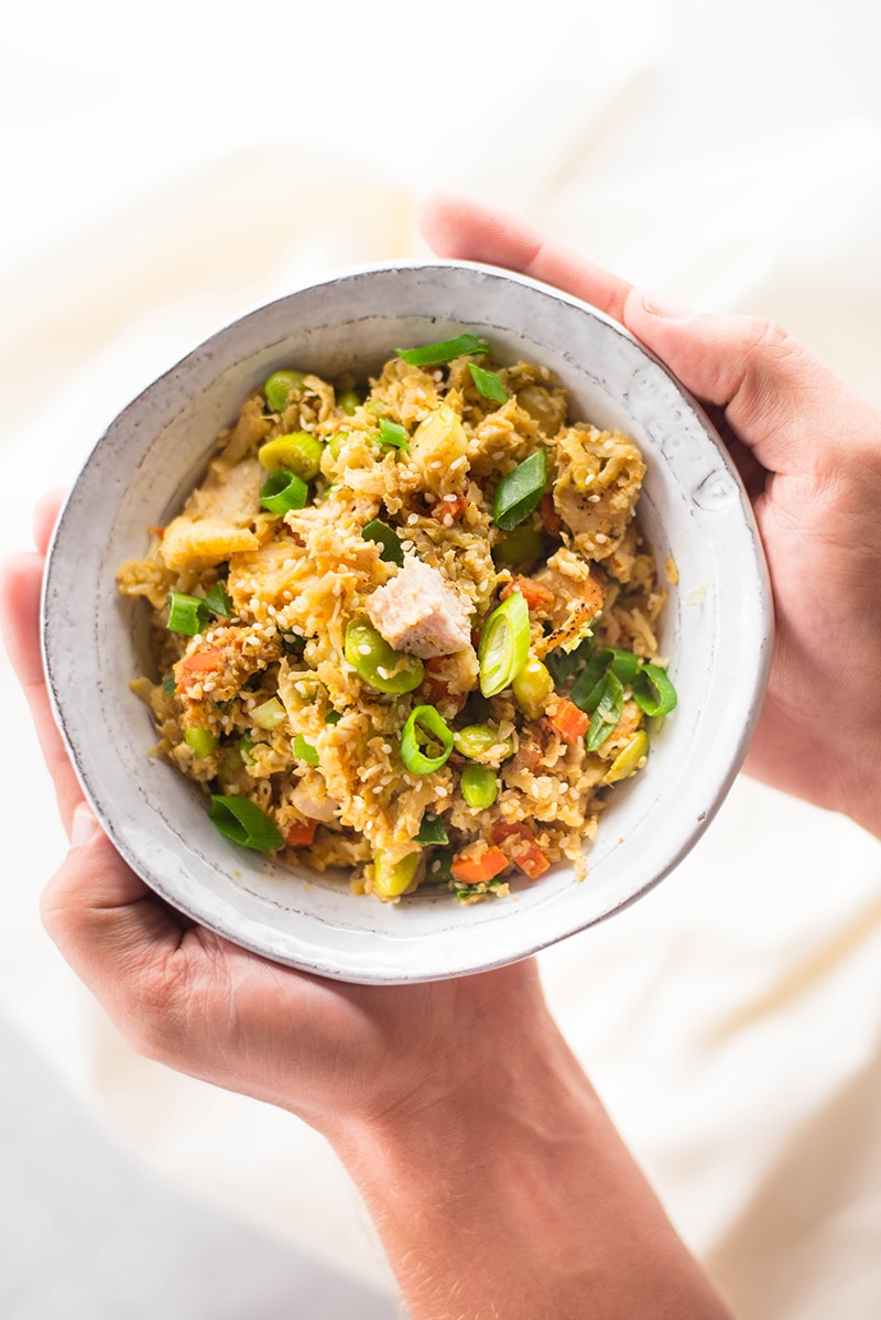 Two hands holding a bowl of chicken cauliflower fried rice with carrots, sliced green onions, cauliflower rice, edamame, and egg.