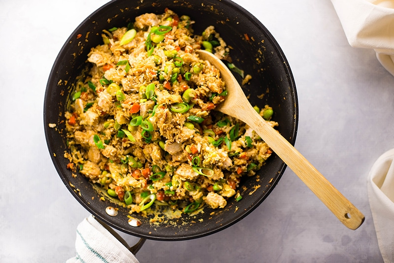 Horizontal image of a skillet of cauliflower chicken fried rice which is cooked and ready to eat. The cauliflower fried rice is topped with sliced green onions.