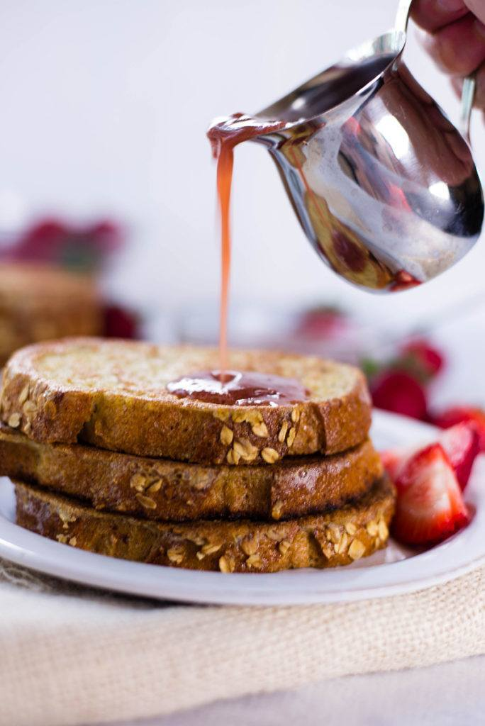 View of pure maple syrup being poured on 3 slices of Strawberry French Toast, a Healthy Breakfast Idea.