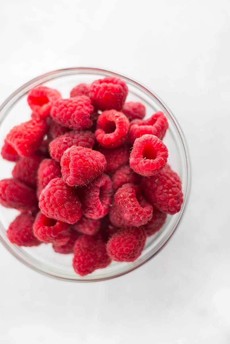 Overhead image of a glass bowl full of raspberries, ready to be frozen for use in smoothies.