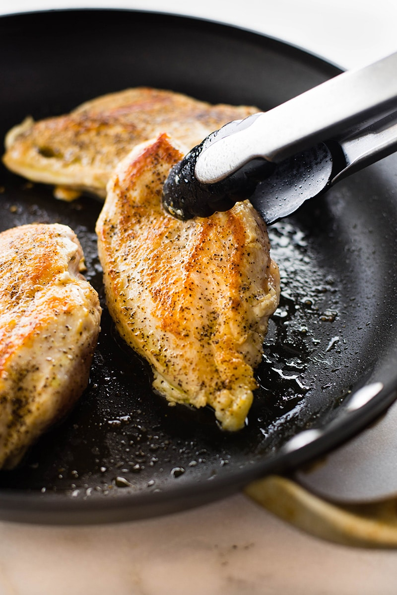 Side angle view of a skillet that is cooking seasoned boneless skinless chicken breast and one of the cooked chicken breasts which is golden brown is being grabbed by a pair of tongs.